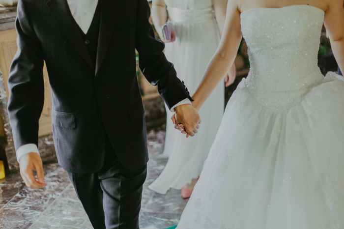 A couple walking down the aisle on their wedding day [SOURCE/PEXELS.COM]