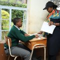 Education CS Amina Mohamed with a candidate during KCSE exams